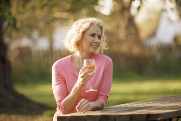 A mature woman drinking a glass of wine outside