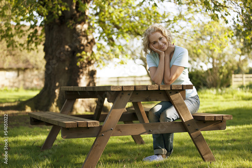 A mature woman sitting at a garden bench smiling