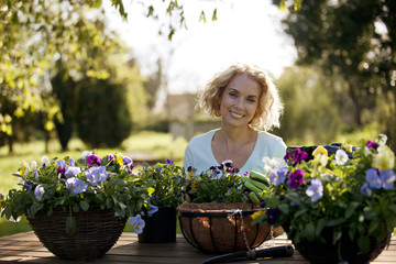 A mature woman planting hanging baskets