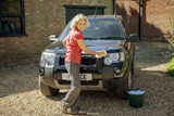 A mature woman washing a four wheel drive car