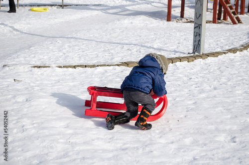 boy with blue jacket knelt down to red sleigh