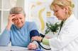 Ärztin misst den Blutdruck und Puls bei Patientin