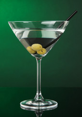 Martini glass with olives on dark green background