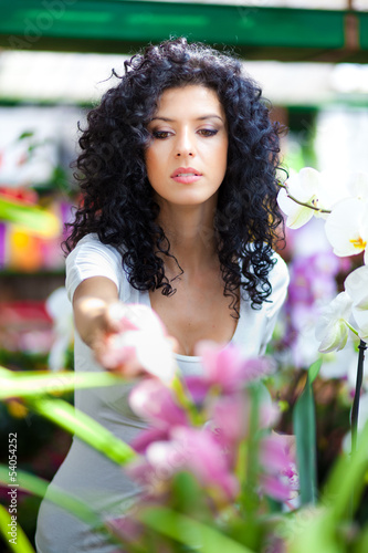 Woman choosing flowers in a greenhouse
