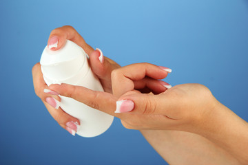 Woman applying cream on hands on color background