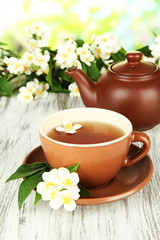 Cup of tea with jasmine, on wooden table, on bright background