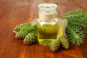 Bottle of fir tree oil and green cones on wooden background