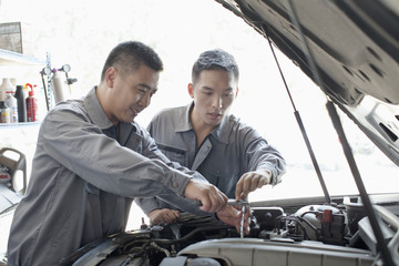 Two Garage Mechanics Working on Engine