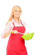 Blond woman wearing red apron and holding kitchen utensil