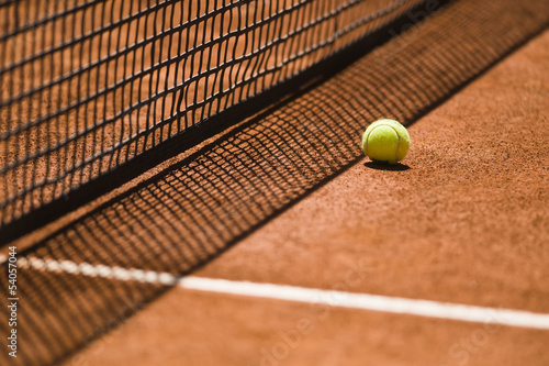 Tennis Ball and Net on a Clay Court