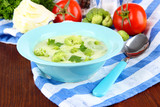 Cabbage soup in plates on napkin on wooden table