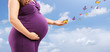 Pregnant woman holding her belly and butterflies on her hand