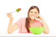Smiling female sitting on a table and eating fresh salad