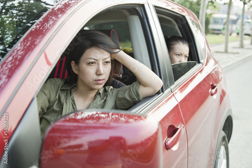 Mother and Daughter Looking Frustrated Out the Window of a Car