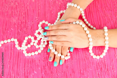 Beautiful woman hands with blue manicure holding beads,