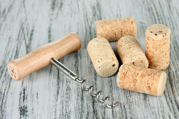 Corkscrew with wine corks on wooden table close-up