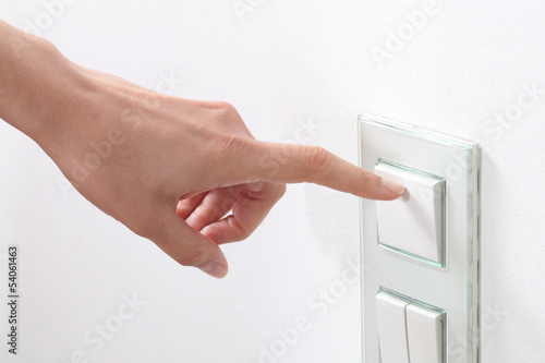 Woman hand turning operating a wall switch