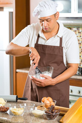 Asian man baking cake in home kitchen