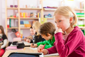 Schulkinder und Lehrerin lernen an der Schule