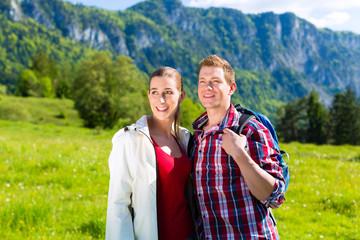 Paar läuft auf Wiese vor Bergpanorama