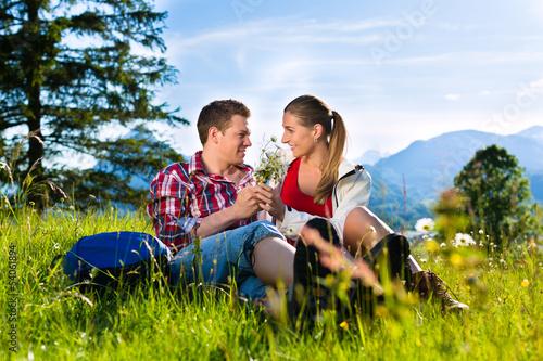 Glückliches Paar sitzt in auf Wiese vor Bergpanorama
