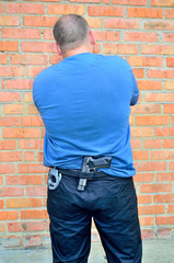 man standing back with a pistol and handcuffs in his belt