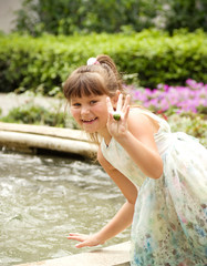 little happy girl in garden with water fall