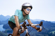 portrait of young woman cycling over the mountains