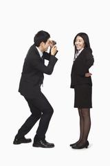 Businessman photographing businesswoman
