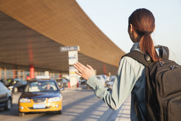 Young traveler hailing a taxi at airport