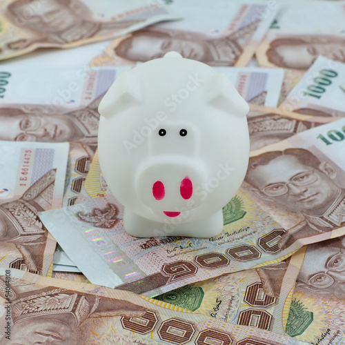 Piggy bank placed up to Thai money background.