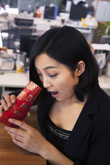Young businesswomen looking into traditional red envelopment, Chinese New Year