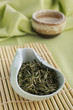 Loose green tea leaves on bamboo tray