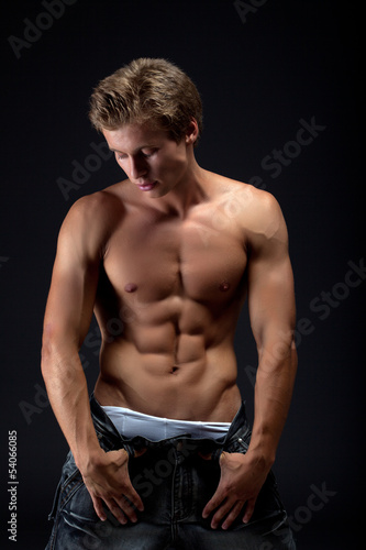 Handsome muscular blond man posing take off jeans