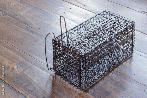 Rat cage trap on the old wooden background.