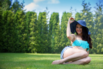 Sexy woman lin hat laying on grass