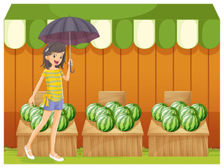 A girl holding an umbrella walking in front of the watermelon sh
