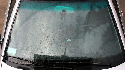 Rain drops running down a car window pane