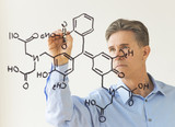 Scientist Drawing Molecular Structure On Transparent Board