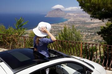 Donna che ammira costa siciliana dal tettuccio automobile