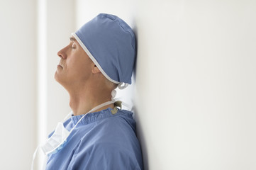 Surgeon With Eyes Closed Leaning On Wall In Ho
