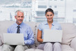 Business people sitting on sofa using their laptops and smiling