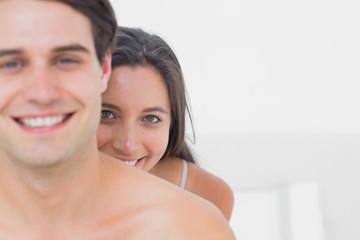 Pretty woman hiding behind shirtless partner