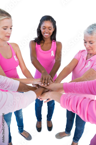 Happy women wearing pink and ribbons for breast cancer putting h