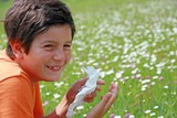 child with an allergy to pollen while sneeze in the middle of th