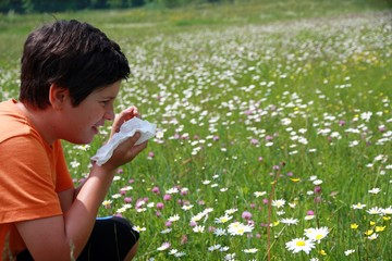 allergic child to pollen and flowers with a handkerchief while s