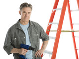 Confident Carpenter Holding Drill While Standing By Ladder
