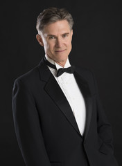 Handsome Man In Tuxedo Standing Against Black Background