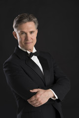 Confident Mature Man In Tuxedo Standing Arms Crossed