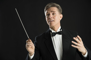 Music Conductor Looking Away While Directing With His Baton